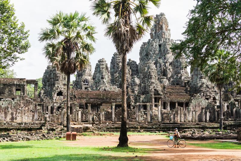 Ung kvinna som cyklar bredvid Bayon-templet i Angkor Wat-komplexet, Kambodja royaltyfria foton