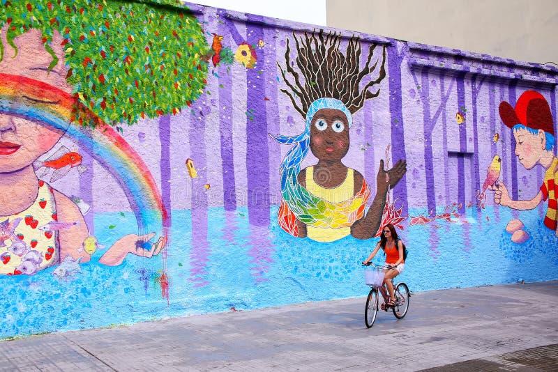 Ung kvinna som cyklar längs den färgrika väggen i Montevideo, Uruguay arkivbilder