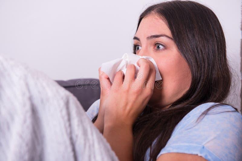 Ung kvinna som dåligt hemma ligger på soffan royaltyfria bilder
