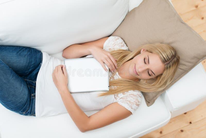 Ung kvinna som dåsar på soffan royaltyfria foton