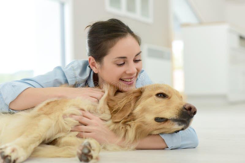 Ung kvinna som daltar hunden på golvet fotografering för bildbyråer