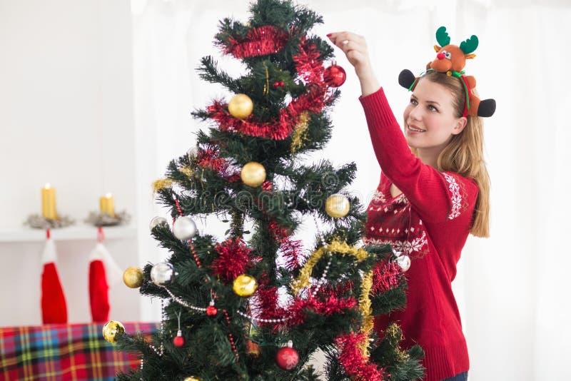 Ung kvinna som dekorerar en julgran royaltyfria foton