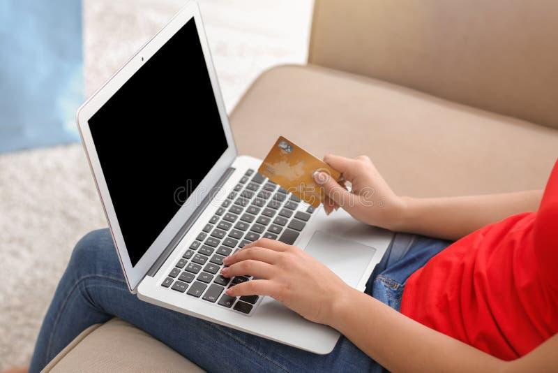Ung kvinna som direktanslutet hemma shoppar med kreditkorten och bärbara datorn, closeup arkivfoto