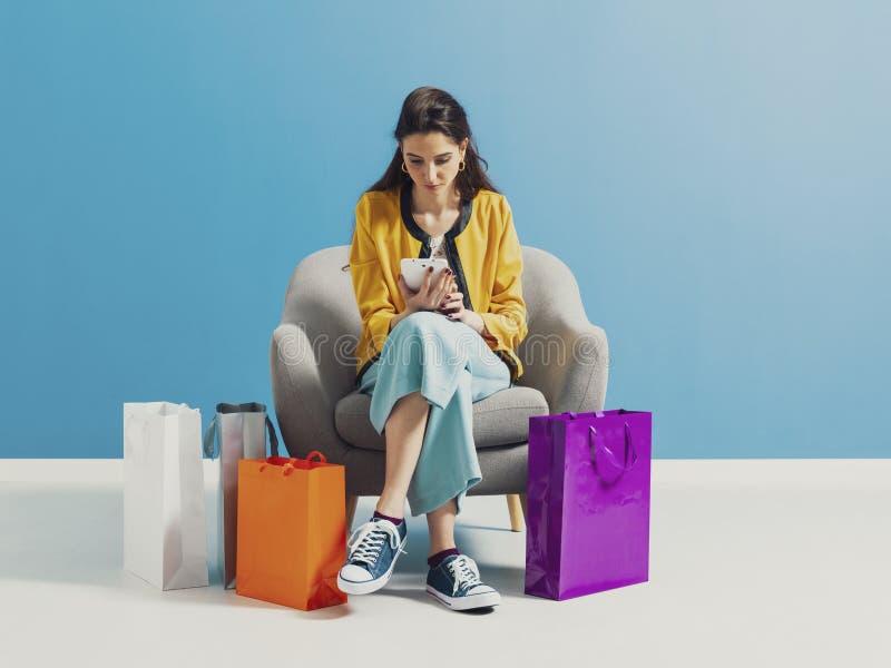 Ung kvinna som direktanslutet kontrollerar modeshoppingförsäljningar royaltyfri bild