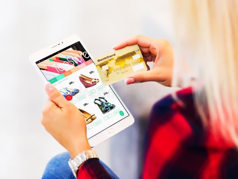 Ung kvinna som direktanslutet shoppar med den minnestavladatoren och kreditkorten royaltyfri foto