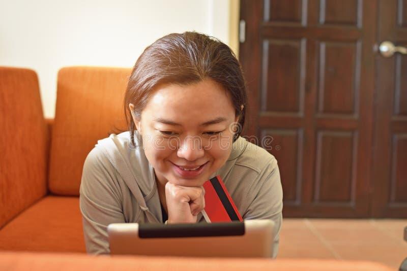 Ung kvinna som direktanslutet shoppar med kreditkorten royaltyfri bild