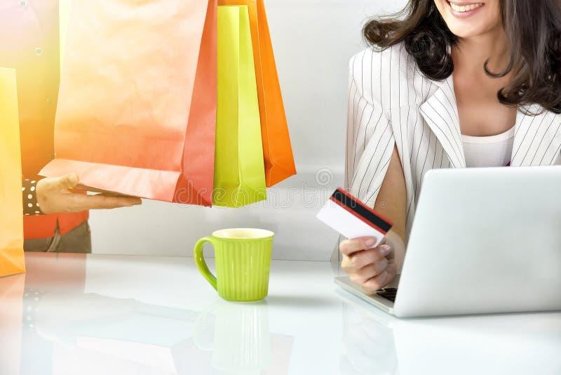 Ung kvinna som direktanslutet shoppar med kreditkorten som beställer direktanslutet royaltyfria bilder