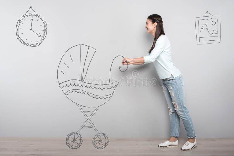 Ung kvinna som drömmer av att bli en moder och att föreställa en barnvagn fotografering för bildbyråer