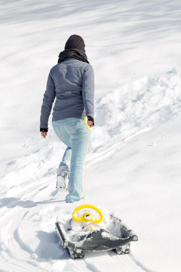 Ung kvinna som drar en pulka i den djupa snön, backview arkivbilder