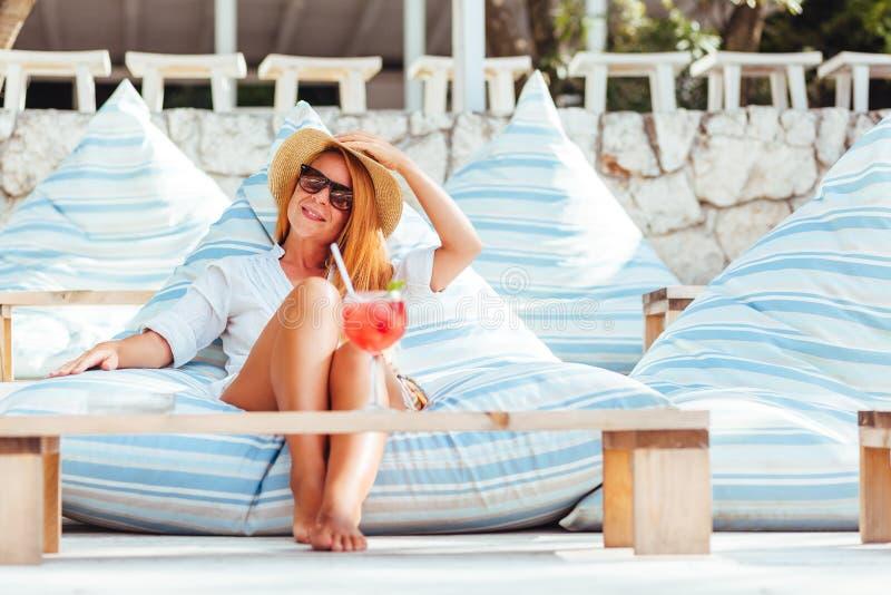 Ung kvinna som dricker coctailen i en strandstång royaltyfri bild