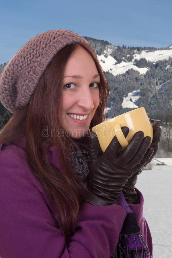 Ung kvinna som dricker en kopp av varmt te i berg i vinter royaltyfri foto