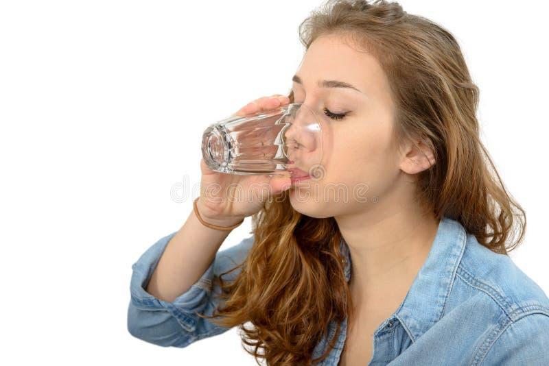 Ung kvinna som dricker ett exponeringsglas av vatten, på vit royaltyfri bild