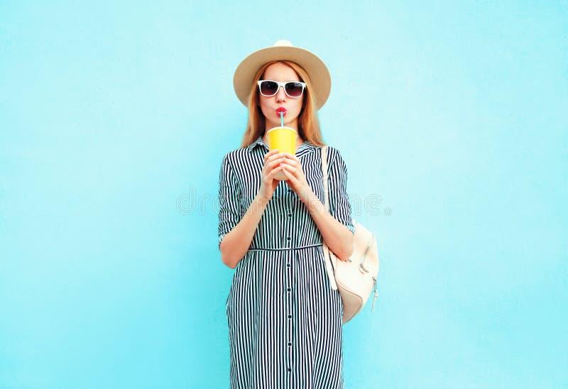 Ung kvinna som dricker fruktfruktsaft från koppen, bärande hatt för sommarrundasugrör, randig klänning på den blåa väggen royaltyfri bild