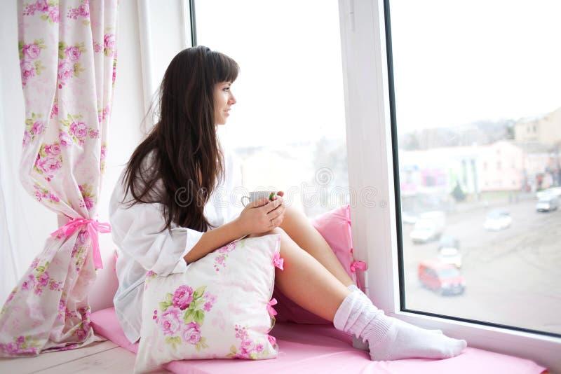 Ung kvinna som dricker hennes morgonkaffe arkivfoton