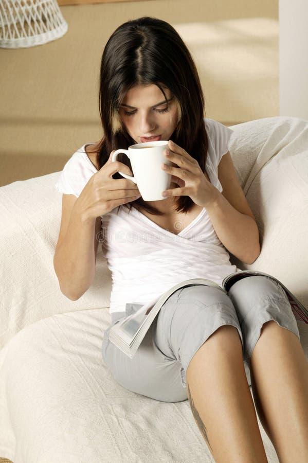 Ung kvinna som dricker kaffe arkivbilder