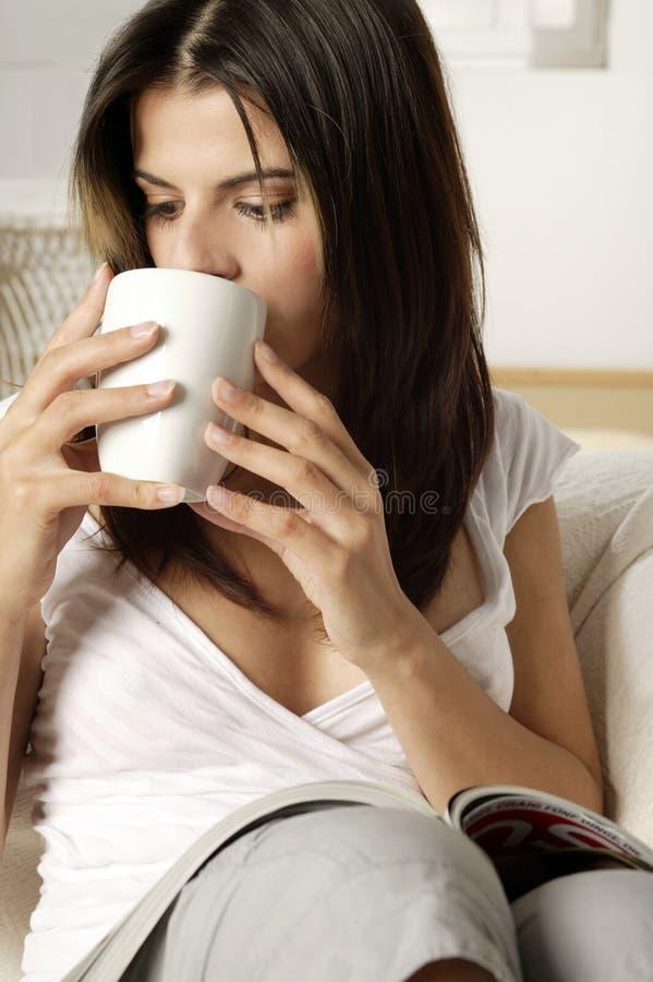 Ung kvinna som dricker kaffe arkivfoto