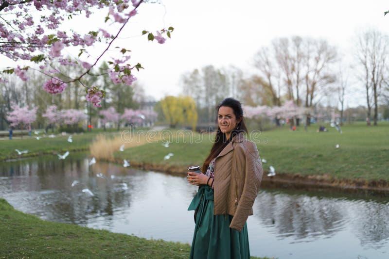 Ung kvinna som dricker kaffe från för smaragdfärg för pappers- kopp en bärande kjol - den färgrika sakura körsbärsröda blomningen royaltyfria bilder