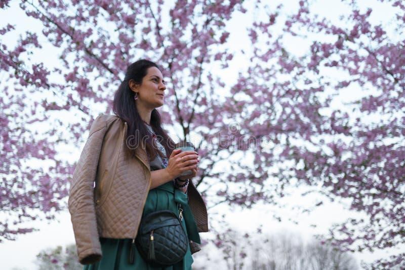 Ung kvinna som dricker kaffe fr?n f?r smaragdf?rg f?r pappers- kopp en b?rande kjol - den f?rgrika sakura k?rsb?rsr?da blomningen royaltyfria foton