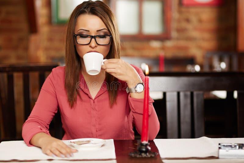 Ung kvinna som dricker kaffe i en restaurang arkivbilder