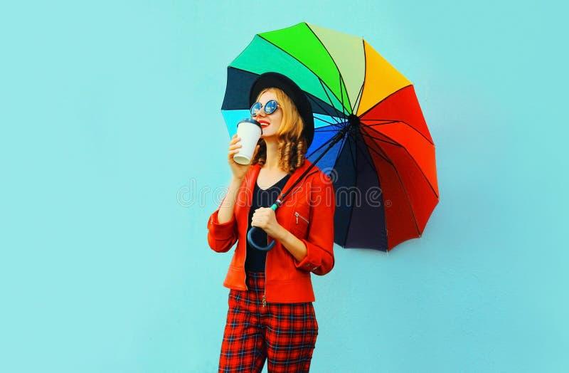 Ung kvinna som dricker kaffe och rymmer det färgrika paraplyet som går i det röda omslaget, svart hatt på den blåa väggen royaltyfri foto