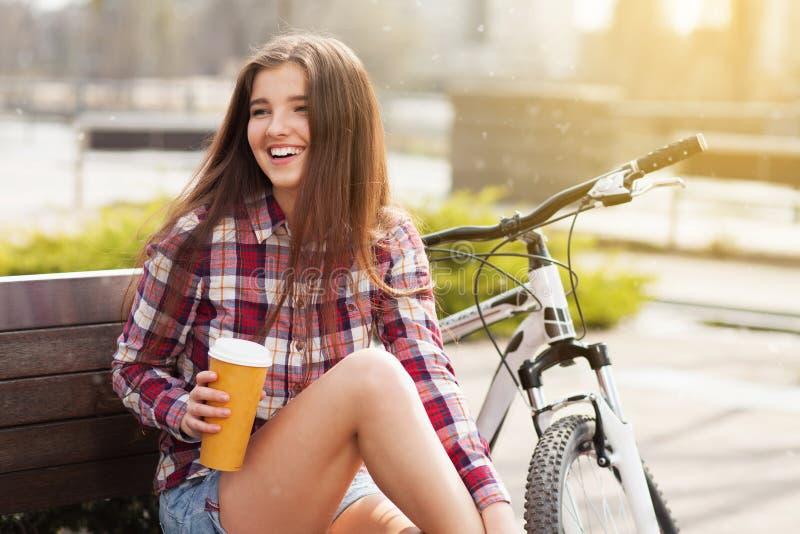 Ung kvinna som dricker kaffe på en cykeltur royaltyfri bild