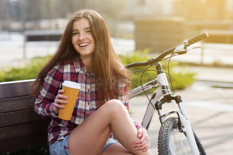 Ung kvinna som dricker kaffe på en cykeltur arkivbild