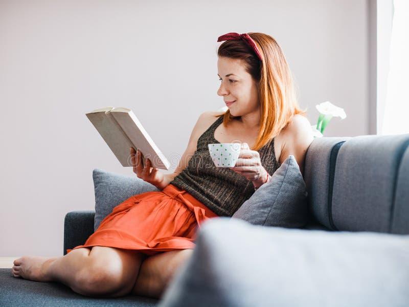 Ung kvinna som dricker kaffeläseboken royaltyfri foto