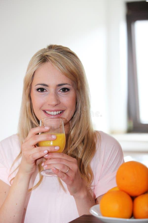 Ung kvinna som dricker ny orange fruktsaft royaltyfri fotografi
