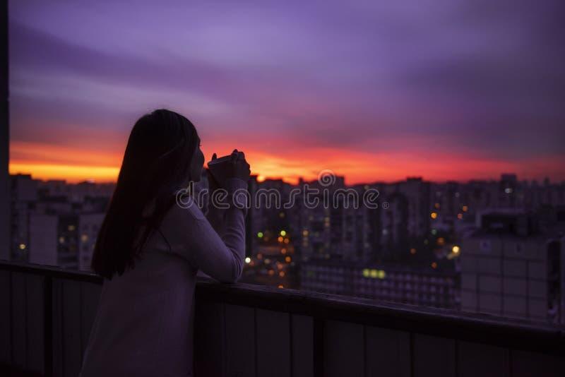 Ung kvinna som dricker te och håller ögonen på solnedgången royaltyfri foto