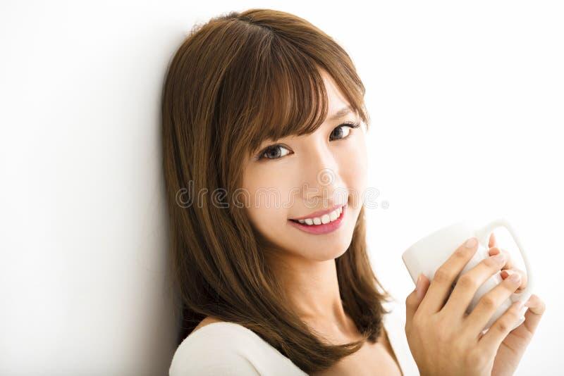 Ung kvinna som dricker varmt lattekaffe royaltyfria bilder