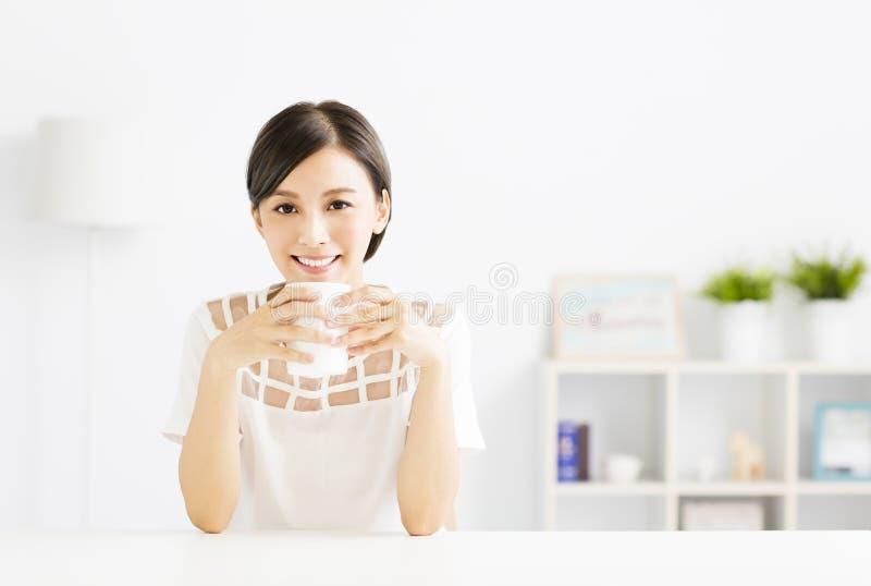 Ung kvinna som dricker varmt lattekaffe i vardagsrum royaltyfria foton