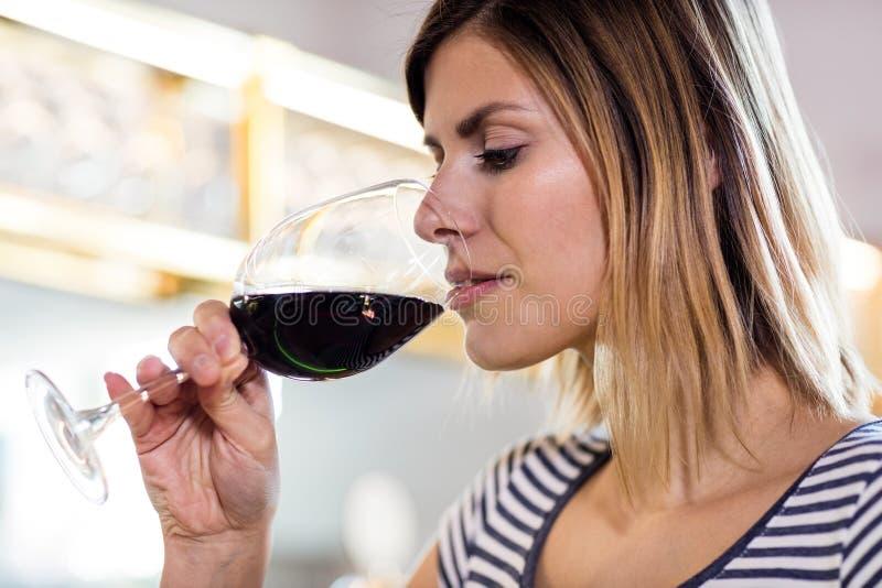 Ung kvinna som dricker vin på restaurangen arkivbild