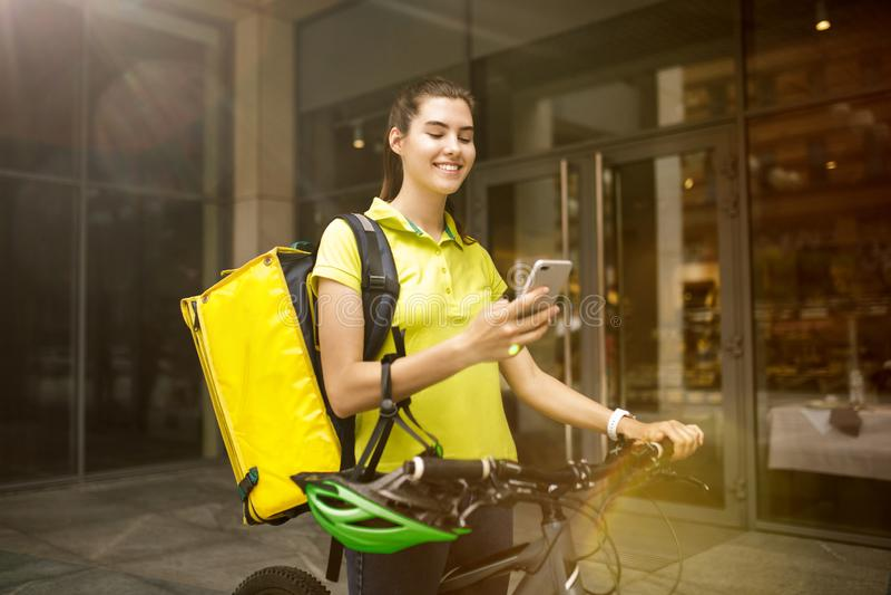 Ung kvinna som en kurir som levererar grejer för använda för mat arkivfoton