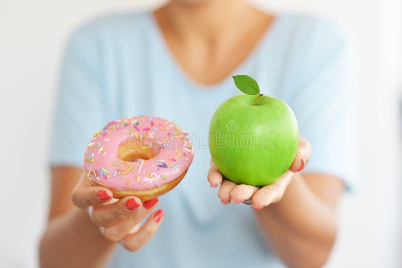 Ung kvinna som erbjuder en attraktiv rosa munk och håller för henne ett sunt organiskt grönt äpple arkivfoton