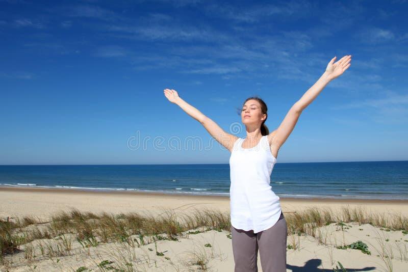 Ung kvinna som excercising på stranden arkivbild