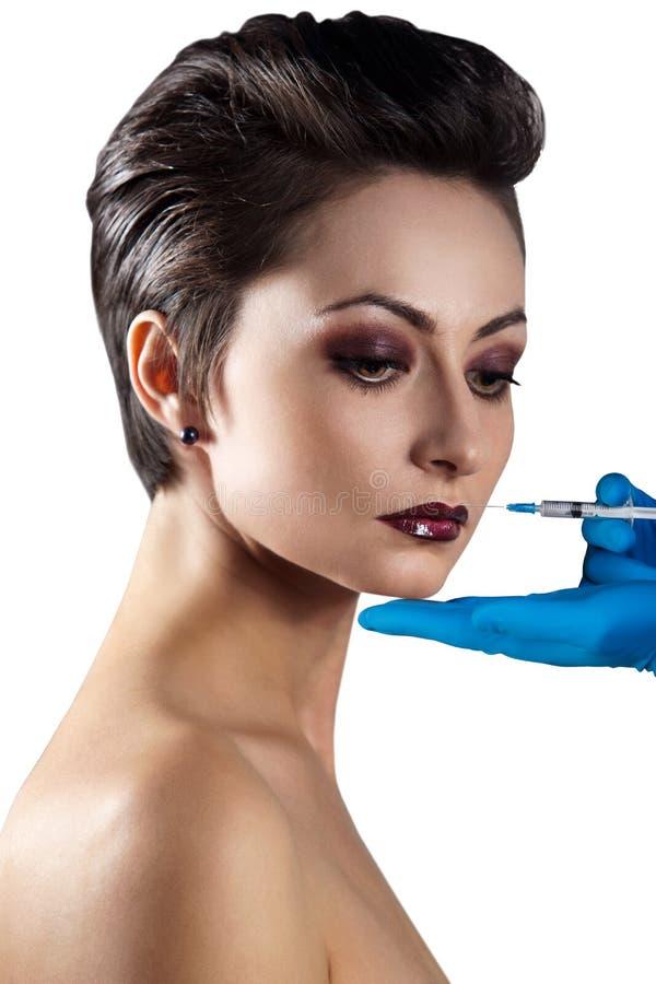Ung kvinna som får den kosmetiska injektionen royaltyfria foton