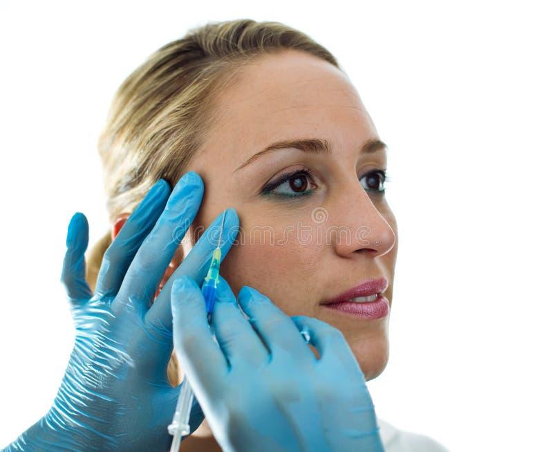 Ung kvinna som får en botoxbehandling royaltyfri bild