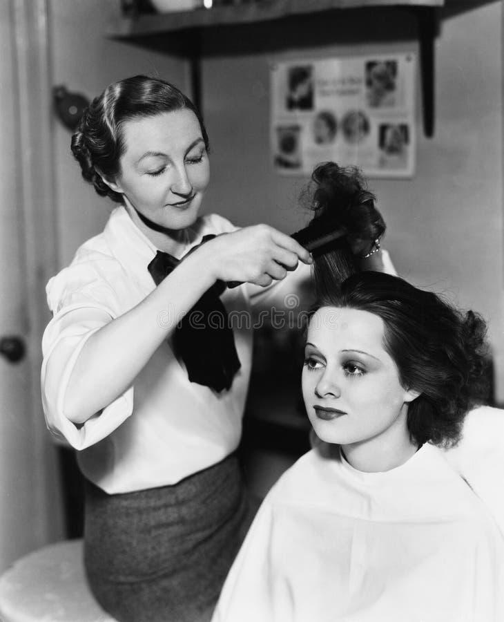 Ung kvinna som får henne gjord i en hårsalong (alla visade personer inte är längre uppehälle, och inget gods finns Leverantörwarr royaltyfria bilder