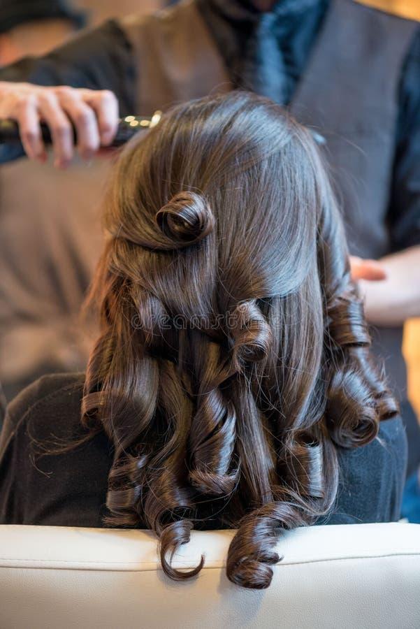 Ung kvinna som får henne hår gjort arkivbild