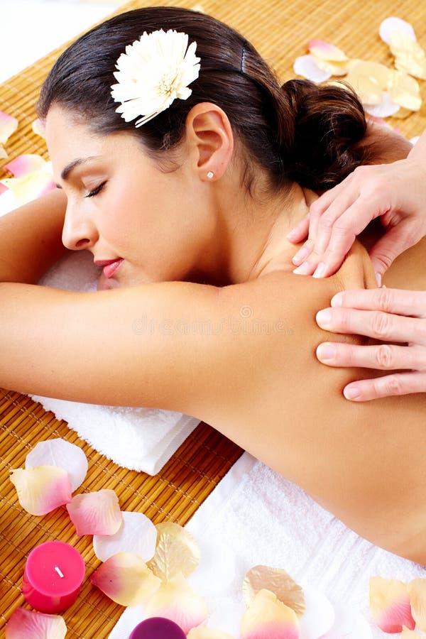 Ung kvinna som får massage i brunnsortsalong. arkivfoton