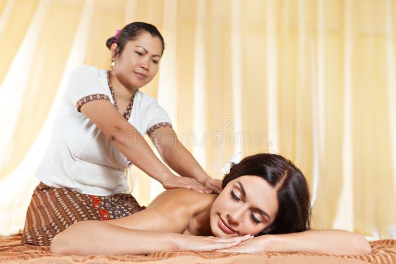 Ung kvinna som får massage i thailändsk brunnsort arkivfoton