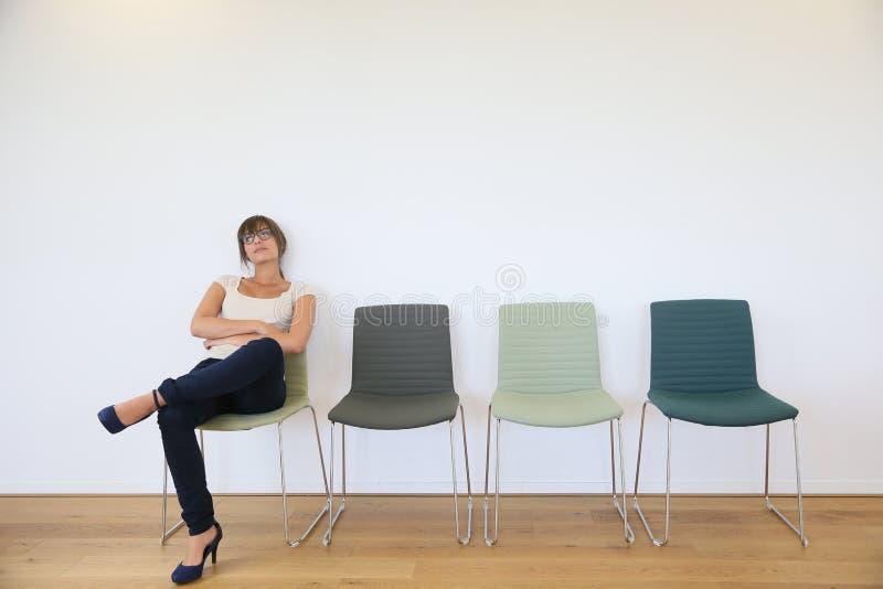 Ung kvinna som får uttråkat sammanträde i väntande rum arkivbild