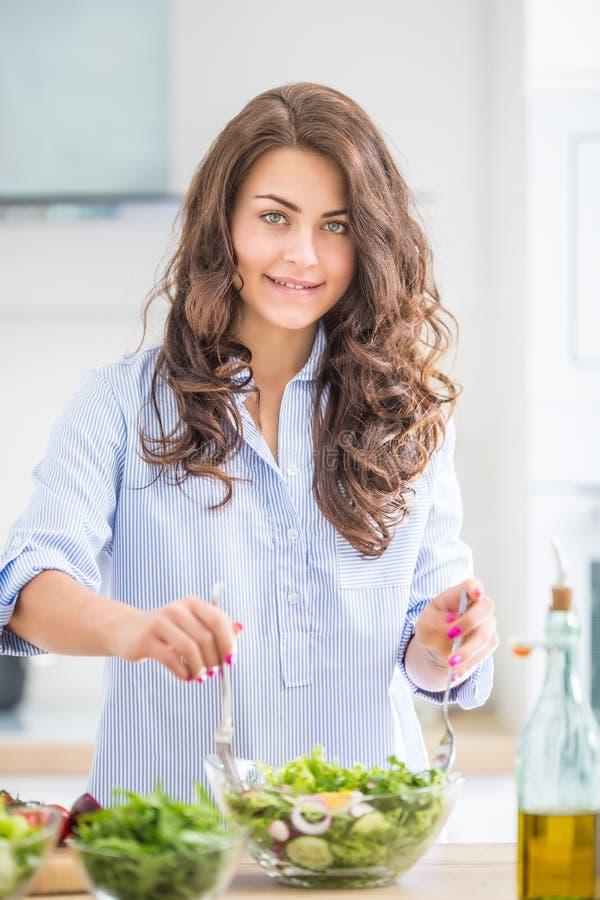 Ung kvinna som förbereder grönsaksallad i hennes kök Härlig kvinna för sunt livsstilbegrepp med den blandade grönsaken arkivfoto