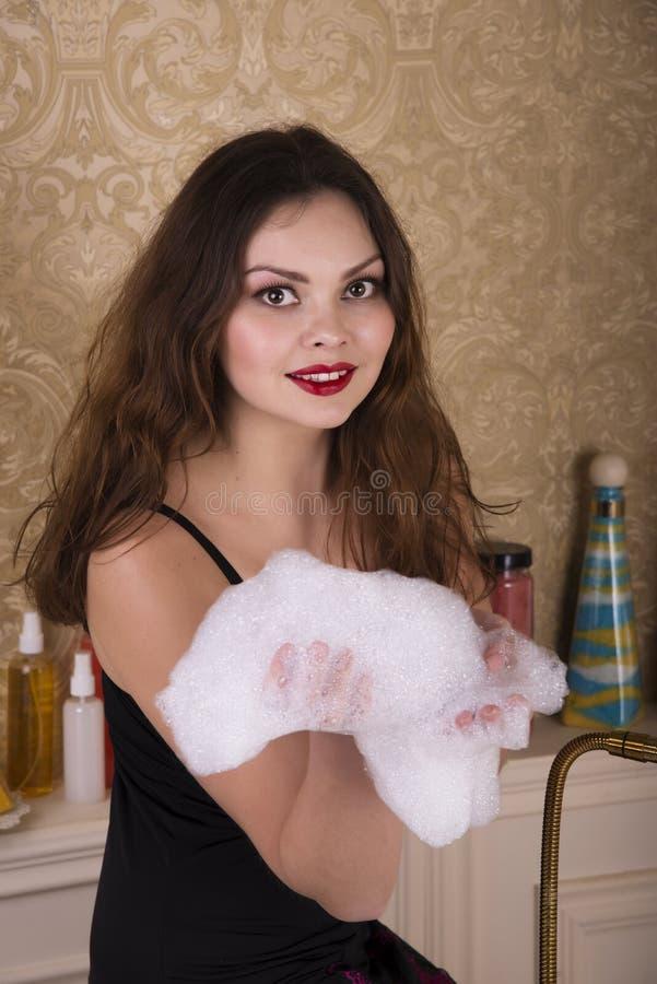 Ung kvinna som förbereder sig att ta ett bad arkivbild