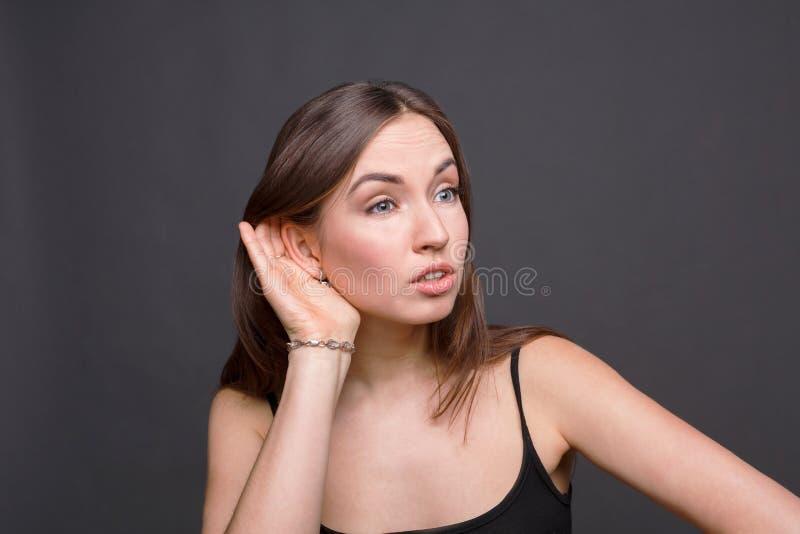 Ung kvinna som försöker att lyssna skvaller royaltyfria bilder