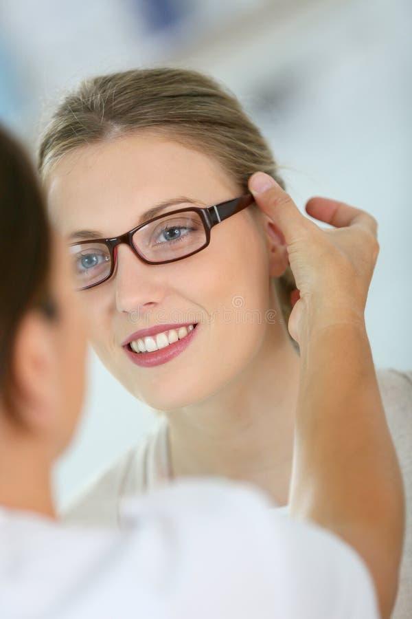 Ung kvinna som försöker på glasögon arkivbild