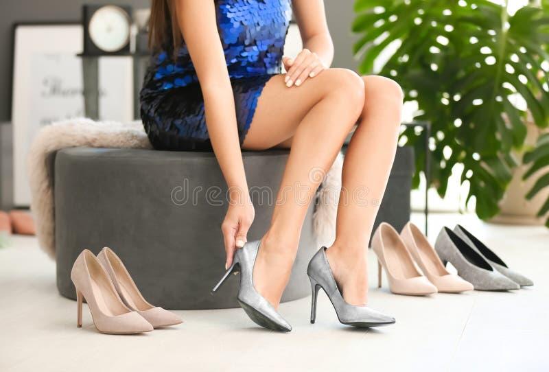 Ung kvinna som försöker på hög-heeled skor royaltyfri foto