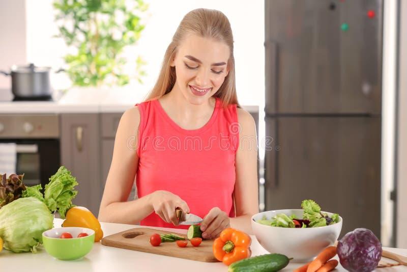 Ung kvinna som f?rbereder sallad i k?k Banta matbegreppet arkivfoton