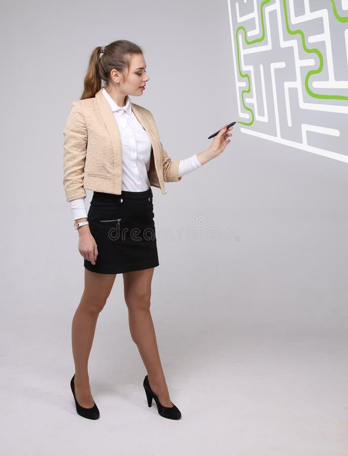 Ung kvinna som finner labyrintlösningen som skriver på whiteboard arkivfoton