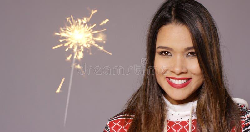 Ung kvinna som firar jul med ett tomtebloss royaltyfri bild